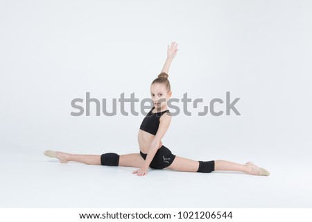 Rhythmic gymnastics caucasian blonde girl in black suite performing athlete exercises showing twine flexibility and stretching abilities acrobat balance on white background isolated