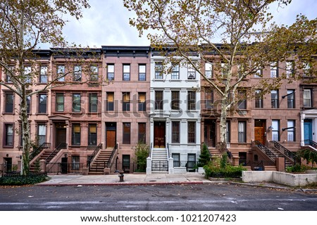 a view of a row of historic brownstones in an iconic neighborhood of Manhattan, New York City #1021207423