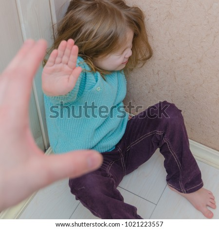 a child hides in the corner of the house, hand making a stop gesture, and social issues #1021223557