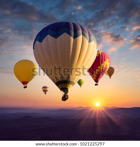 Hot air balloons above ultraviolet mountain silhouettes in golden sunlight. Sunrise in bright colors for your stories about travel dreams, active leisure or adventure. #1021225297
