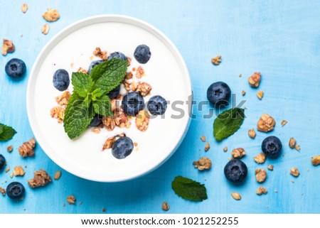 Greek yogurt granola and blueberries on blue table. #1021252255