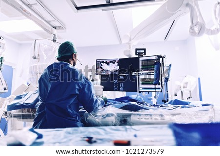 Cardiologist doing catheter ablation with radiofrequency energy using imaging system with fluoroscopic X-ray tube for interventional vascular procedures and electrophysiology. image guided system #1021273579