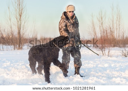 black riesenschnauzer dog with his master on a walk on winter snowy day #1021281961