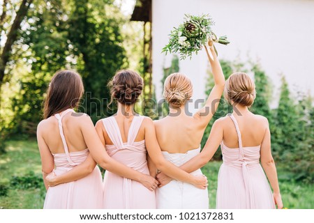 bride standing with her back in a white wedding dress and raised hand with three bridesmaids #1021372831
