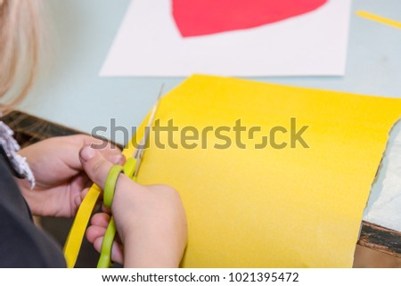 The child cuts out of paper. The child is engaged in needlework. the child makes a postcard on 14 February. #1021395472