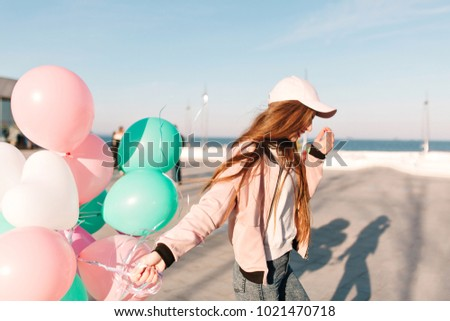 Slim trendy girl in stylish pink clothes walking along the ocean wharf enjoying windy morning in weekend. Charming young long-haired woman running at the sea pier waving bunch of party balloons #1021470718