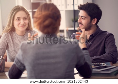 Young couple discussing with a female agent Royalty-Free Stock Photo #1021502443