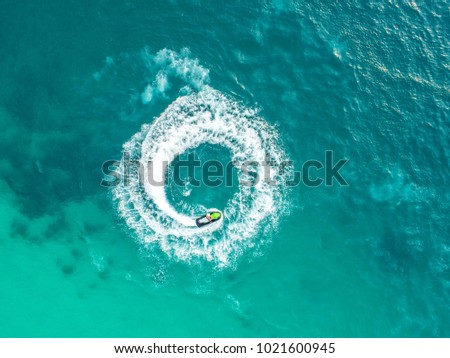 People are playing a jet ski in the sea.Aerial view. Top view.amazing nature background.The color of the water and beautifully bright. Fresh freedom. Adventure day.clear turquoise at tropical beach #1021600945