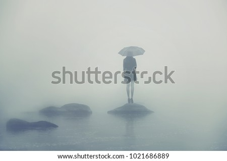 Girl with umbrella standing on a rock in the middle of the water. Alone woman in the fog #1021686889
