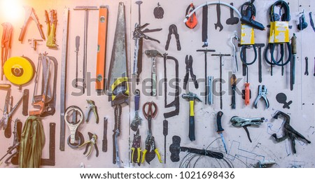 Old tools hanging on wall in workshop.Something's gone. Tools concept #1021698436