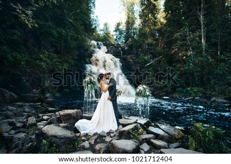 Wedding Beautiful couple sexy Bride dress young girl Brutal groom with beard and gray. Stylish man in costume on the nordic Karelian nature landscape background. waterfall wedding river current  #1021712404