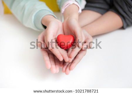 child holding red heart, closeup. Adoption concept #1021788721