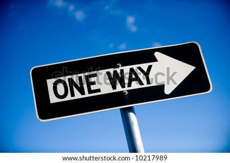 Image of a slightly angled one way sign against blue sky