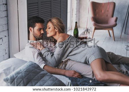 Enjoying lazy Sunday together.  Beautiful young couple embracing while lying on the bed at home #1021843972