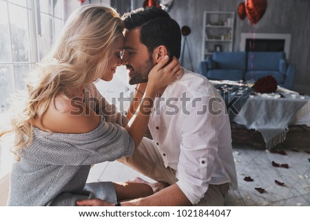 Loving everything about her. Beautiful young couple bonding and smiling while sitting in the bedroom Royalty-Free Stock Photo #1021844047