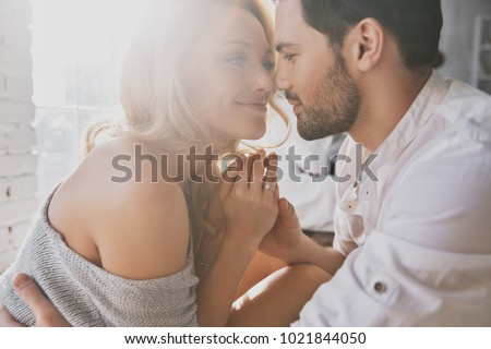 Real love. Beautiful young couple bonding and smiling while sitting in the bedroom Royalty-Free Stock Photo #1021844050