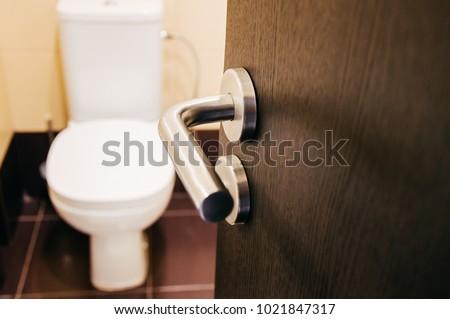 Door handle open to toilet can see toilet #1021847317