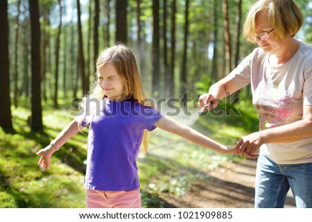 Middle age woman applying insect repellent to her granddaughter before forest hike beautiful summer day. Protecting children from biting insects at summer. Active leisure with kids. #1021909885