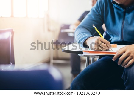 soft focus.high school or university student holding pencil writing on paper answer sheet.sitting on lecture chair taking final exam attending in examination room or classroom.student in uniform #1021963270