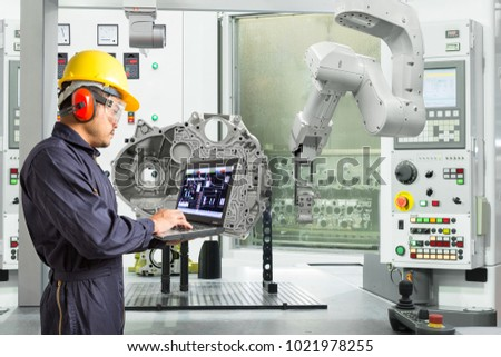 Engineer using laptop computer control automatic robotic hand with CNC machine in automotive industry, Smart factory concept #1021978255