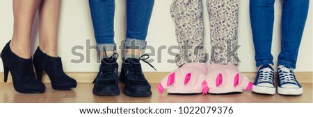 Female legs in cute pink monster foot slippers with big claws and other in different kind of shoes. Be original concept. Standing out of the croud - individuality. Royalty-Free Stock Photo #1022079376