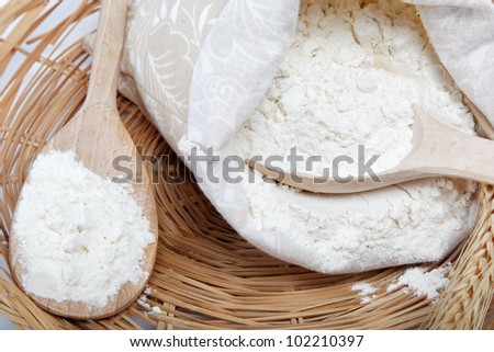 Flour and wheat grain with wooden spoon on a wicker basket. #102210397
