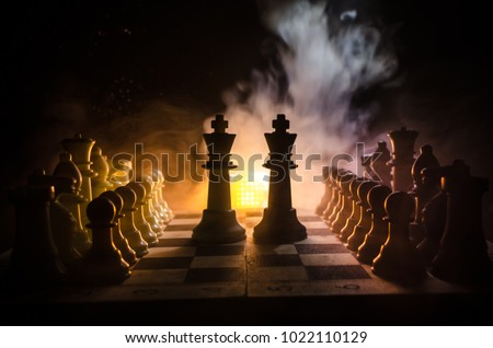 Chess board game concept of business ideas and competition and strategy ideas concep. Chess figures on a dark background with smoke and fog. Selective focus #1022110129
