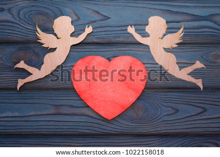 two cupids and a red heart made of wood texture. A celebration of love. Valentine's day.