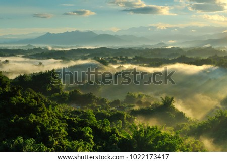 The blue sky of the sun shines in the misty ridge of the mountains and jungle, the cloud is very beautiful color. #1022173417