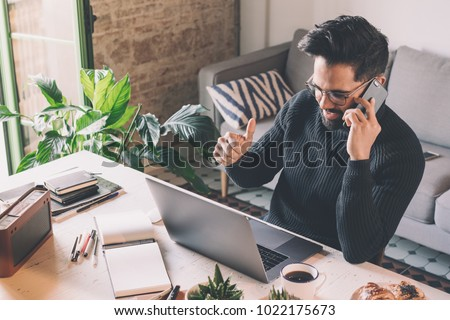 Bearded coworker man working at living room at home. Man sitting at wooden table using laptop and mobile phone. Blurred background