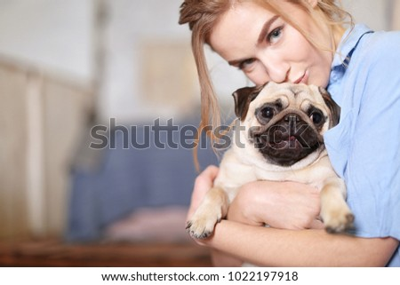 Young woman with cute pug dog at home. Pet adoption #1022197918