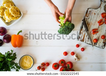 Top view womam hands. Food background. Food concept. Various fresh Ingredients for cooking. Picture of kitchen table with colorful vegetables . Sliced vegetables for making meal. Selective focus.