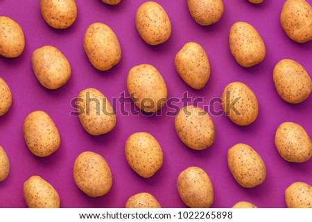 Potato on a colored background. Pattern of potato. Natural potato #1022265898