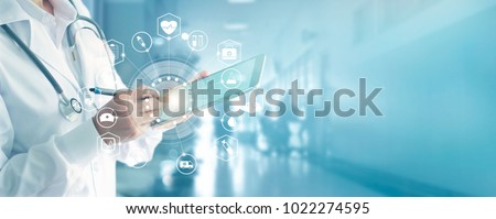 Medicine doctor and stethoscope touching icon medical network connection with modern interface on digital tablet in hospital background. Medical technology network concept Royalty-Free Stock Photo #1022274595