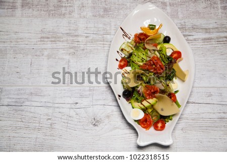 salad with grilled vegetables, fish, eggs, cheese, tomato and olives in a white plate on a wooden background #1022318515