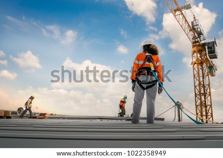 Construction worker wearing safety harness and safety line working on a metal industry roof new warehouse Royalty-Free Stock Photo #1022358949