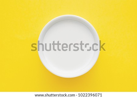 Top down minimalist view of a milk in a white bowl on yellow background #1022396071