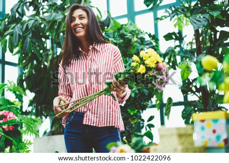 Cheerful creative asian woman designing floral composition working in glasshouse growing fresh plants,successful female owner of flower shop making blooming bouquet satisfied with job in orangery #1022422096