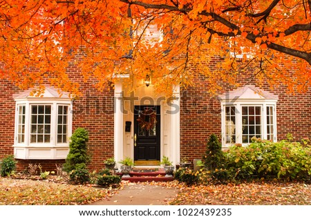 Red brick house entrance with seasonal wreath on door and porch and bay windows on autumn day with leaves on the ground and hydrageas still in bloom - colorful foliage #1022439235