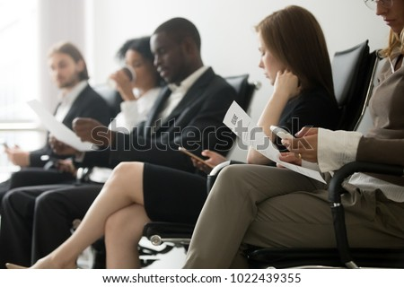 Multi-ethnic applicants sitting in queue preparing for interview, black and white vacancy candidates waiting on chairs holding resume using smartphones, human resources, hiring and job search concept Royalty-Free Stock Photo #1022439355