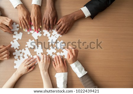 Hands of multi-ethnic team assembling jigsaw puzzle, multiracial group of black and white people joining pieces at desk, successful teamwork concept, help and support in business, close up top view #1022439421