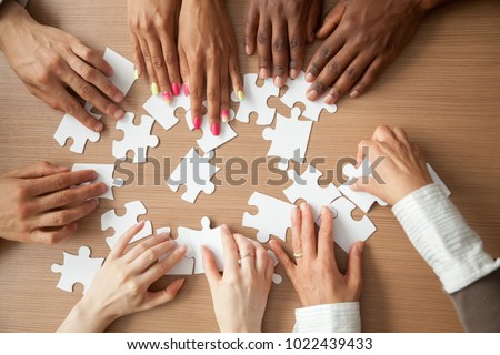 Hands of diverse people assembling jigsaw puzzle, african and caucasian team put pieces together searching for right match, help support in teamwork to find common solution concept, top close up view #1022439433