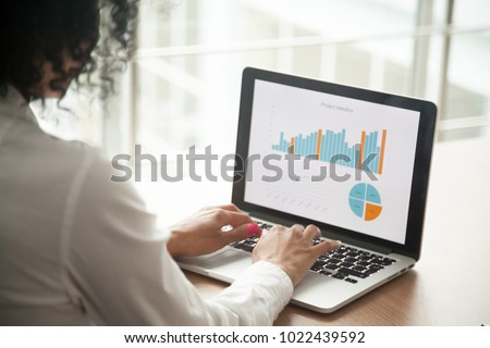 African businesswoman analyzing statistics on laptop screen, working with financial graphs charts online, using business software for data analysis and project management concept, rear close up view #1022439592