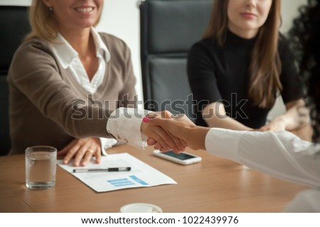 Caucasian hr manager welcoming african applicant at job interview, diverse businesswomen handshaking at group meeting, good first impression and female teamwork, women business partnership concept #1022439976
