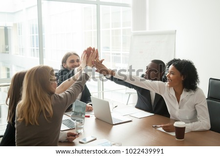 Excited african and caucasian business team giving high five at office meeting motivated by victory, achievement or good work result, multi-ethnic employees group celebrate corporate success together #1022439991