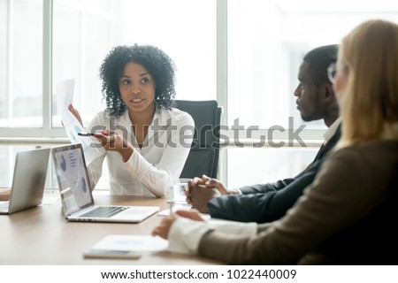 African businesswoman showing good statistics report explaining deal advantages convincing multiracial partners at negotiations meeting, black manager consulting diverse clients promising benefits #1022440009