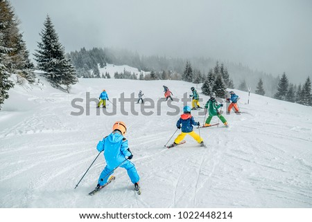 Teaching children skiing. Child skiing in the mountains with instructor. Children learning ski on the slope. mountain ski resort. winter sport.  Kid in ski school. Winter sport for kids. Making turns #1022448214