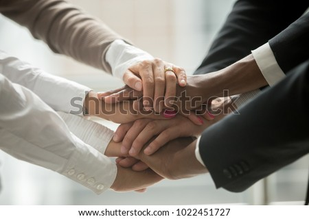 Diverse people putting stacked hands together promising help and support starting common business, black and white multiracial group unite at motivating training, team building concept, close up view #1022451727