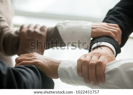 Four multiracial business people holding each others wrists, diverse partners join hands together as concept of reliable support in team, strength, power and unity in collaboration, close up view #1022451757