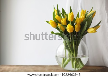 A bouquet of yellow tulips in a vase on the windowsill. A gift to a woman's day from yellow tulip flowers. Beautiful yellow flowers in a vase by the window. #1022463943